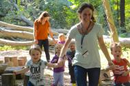 A teacher runs through the forest with students at the University of Delaware's nature-based preschool. (Newark Post)